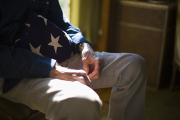 Senior man with a folded American flag
