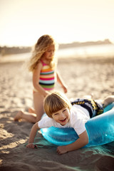 Young boy and girl playing with an inflatable ring on the sand at the beach.