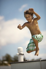 Smiling young boy leaping from a pier into the water.
