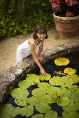 Portrait of a smiling young girl touching a lily pad in a lush garden fishpond.