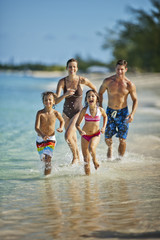 Happy family splashing in shallow water at a tropical beach
