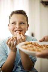 Boy eating food given to him on plate