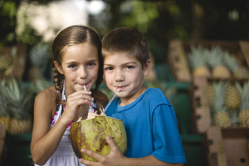 Brother and sister drinking a coconut drink together.