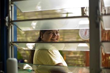 Smiling woman seen through an open slatted window.