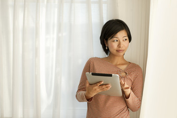 Happy young woman using a digital tablet.