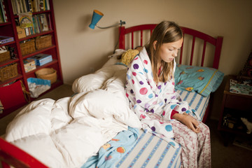 Portrait of depressed girl in pajamas in her bedroom.