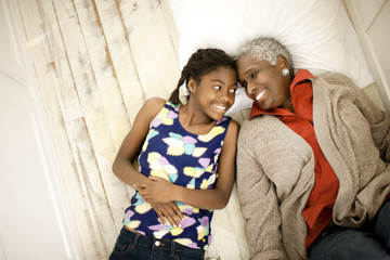 Smiling senior woman lying down next to her teenage granddaughter.
