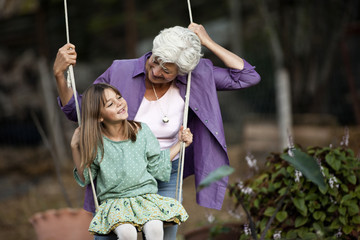 Senior woman pushes her granddaughter on a swing.