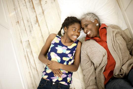Smiling senior woman lying down next to her teenage granddaughter.