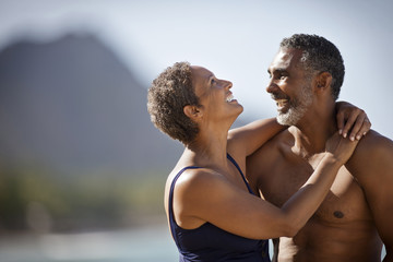 Mature couple hugging on beach.