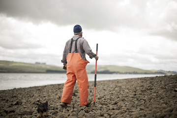 Senior man walking along a rocky shoreline.