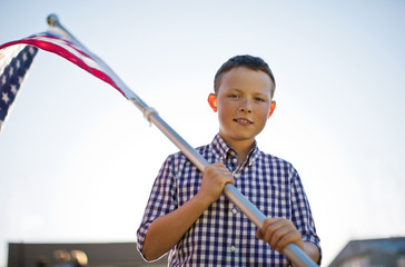 Portrait of a young boy holding an American flag.