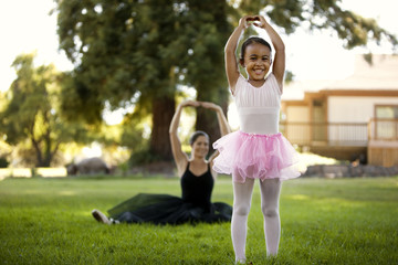 Mid adult woman and her young daughter ballet dancing in a park.