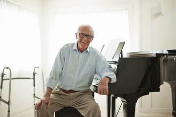 Portrait of a happy senior man playing the piano.