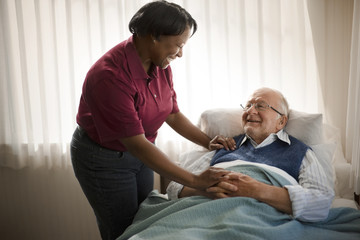 Happy female nurse comforting an elderly patient at his bedside.