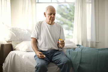 Concerned senior man holding a medicine bottle while sitting on the edge of his bed.