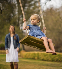 Mother pushing her daughter on a wooden swing.