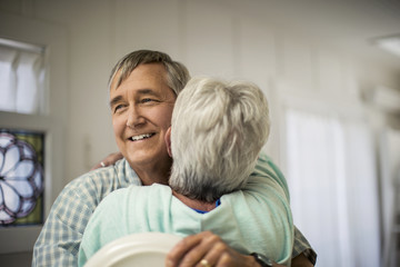 Affectionate mature couple share a spontaneous hug as they finish putting the dishes away.