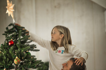 Young girl placing the star on the top of the Christmas tree with her father.