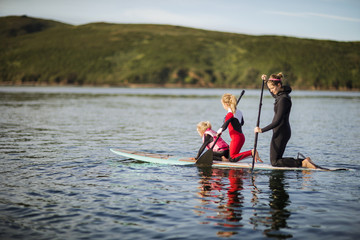 Young woman and her two daughters paddleboarding together on a lake.