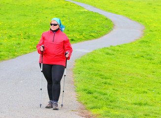 Overweight woman walking on meadows trail. Slimming and active lifestyle theme.