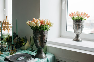 flower arrangement: young fresh colorful tulips in a vintage iron vase, which stands on the windowsill. vesennee the mood of the bouquet of plants. Wallpaper for desktop
