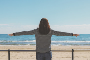 woman facing the sea with open arms