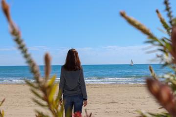 facing the sea looking at a sailboat with sailor jersey