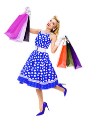 Full body portrait of woman in pin-up style blue dress in polka dot holding shopping bags, isolated on white background