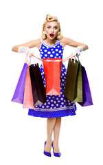 Full body portrait of woman in pin-up style blue dress holding shopping bags