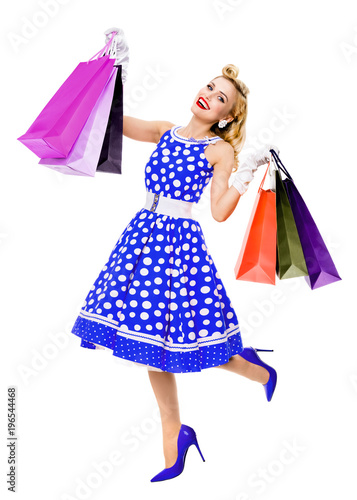 fc10763a3c Full body portrait of woman in pin-up style blue dress in polka dot holding  shopping bags