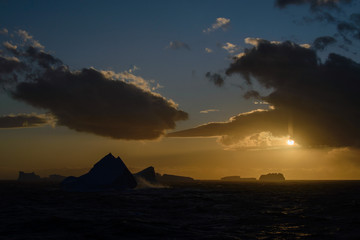 Iceberg at sunset against sun
