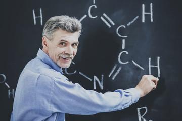 Professor of chemistry writes on the blackboard formula in University