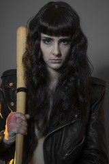 Alone, Juvenile delinquency concept, young brunette teenager with black leather jacket and jeans with a baseball bat