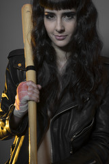 Juvenile delinquency concept, young brunette teenager with black leather jacket and jeans with a baseball bat