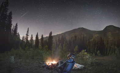 Woman at Campfire in Mountains Looking up at the Stars