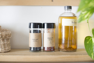 Spices and oil sit on a shelf in the kitchen