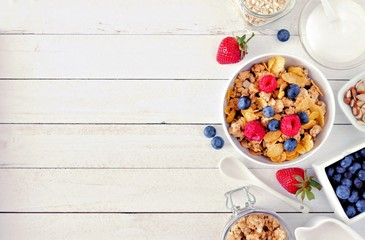 Cereal and ingredients for a healthy breakfast forming a side border over a white wood background. Top view. Copy space.