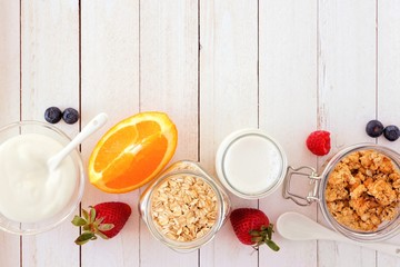 Ingredients for a healthy breakfast  forming a bottom border over a white wood background. Top view. Copy space.