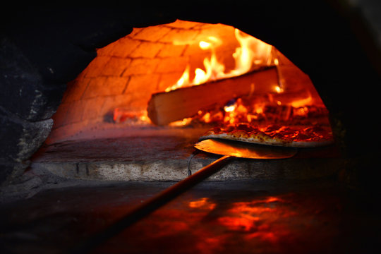 Preparing of a real Italian pizza in a wood-burning stove. An old and authentic restaurant background.