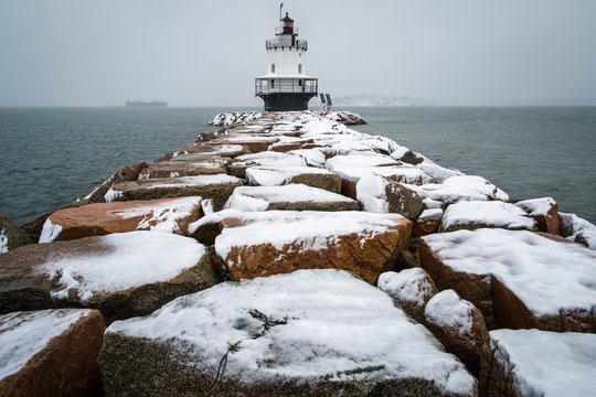A beautifully snowy lighthouse during a storm in Maine.