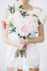 Girl with bouquet of pink and white peony flowers. Front view.