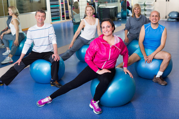 Group of people with balls in fitness club.