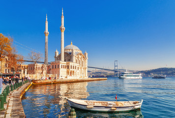 Photo sur Toile Turquie Ortakoy cami - famous and popular landmark in Istanbul, Turkey. Lovely spring scenery with fishing boat at foreground and old historical mosque Ortakoy and Istanbul Bosporus bridge at background.