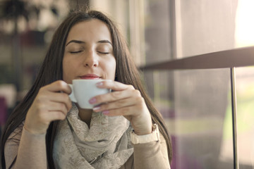 Portrait of young gorgeous female drinking cup of coffee and enjoying her leisure time alone