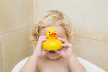 smiling child bathing in the bathroom with foam
