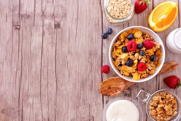 Cereal and ingredients for a healthy breakfast forming a side border over a wood background. Top view. Copy space.