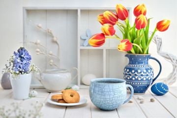 Coffee and cookies on white table with red tulips and springtime decorations
