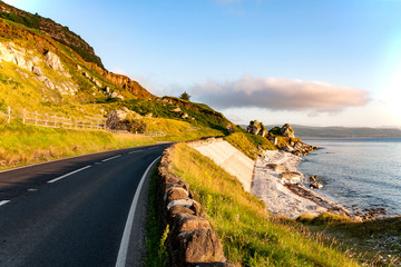 Aluminium Prints Sea The eastern coast of Northern Ireland and Antrim Coastal road a.k.a. Causeway Coastal Route wit rocks and concrete revetment in sunrise light