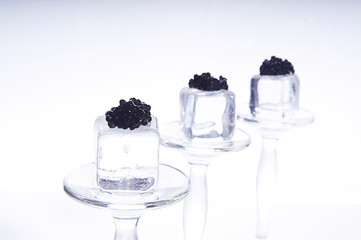 black caviar on ice cubes isolated on white